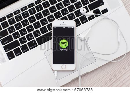 White Iphone 5S With Site Spotify On The Screen And Headphones Lies On The Keyboard Macbook