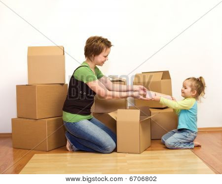 Woman And Little Girl In A New Home Unpacking