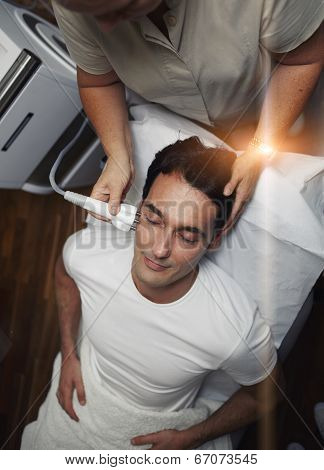 Man having facial laser rejuvenation procedure at clinic