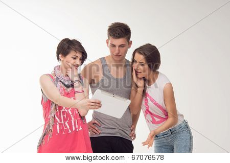 Two attractive teen girls and a boy have fun, isolated on white