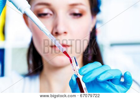 Girl with a pipette in the Genetics  Laboratory. Problem study of the human genome an ethical issue