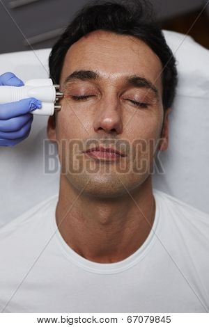 Beautiful man having laser skin treatment in a skincare