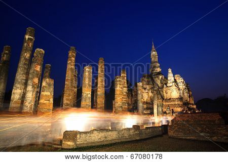 Makha Bucha Day At Sukhothai Historical Park. People Walking Pass The Side Of Buddha Statue In Wian