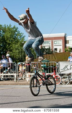 Young Man Stands On Bike Handlebars Practicing For Bmx Competition