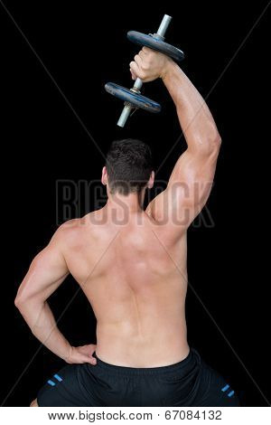 Strong crossfitter lifting up heavy black dumbbell above head on black background
