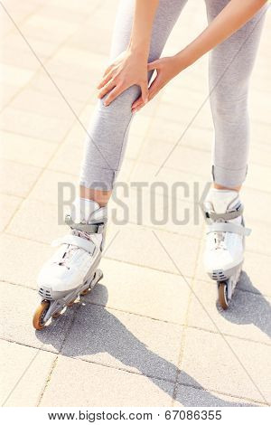A picture of a woman having problem with knee while roller blading