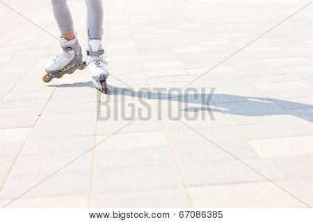 A picture of woman's legs with roller blades on the path