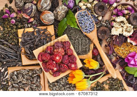 Collection of different dry types tea (green,black, herbal) in wooden spoon on kitchen  table background,  top view