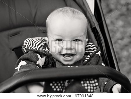 Happy Baby Boy Sitting In A Stroller