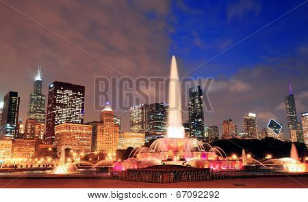 Chicago skyline with skyscrapers and Buckingham fountain in Grant Park at dusk lit by colorful lights.