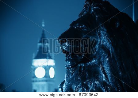 Trafalgar Square lion statue and Big Ben in London at night in BW