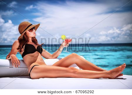 Sexy woman relaxing on luxury beach resort, sitting on lounger and drinking cocktail, summer vacation concept