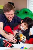 stock photo of babysitting  - Handsome father playing cars with disabled son on floor mat - JPG