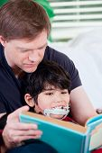 picture of storytime  - Father reading book with disabled son in lap - JPG