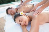 pic of couple  - Attractive couple enjoying couples massage poolside outside at the spa - JPG