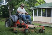 picture of grass-cutter  - Landscaper cutting grass on riding lawn mower  - JPG