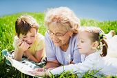 stock photo of granddaughters  - happy grandmother reading book to grandchildren outdoors - JPG