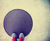 picture of manhole  - a pair of feet on a manhole cover done with a retro vintage instagram filter - JPG
