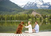 picture of pier a lake  - Senior couple with dog sitting on pier above the mountain lake with mountains in background - JPG