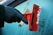 stock photo of ice-scraper  - Gloved hand using an ice scraper on iced glass - JPG