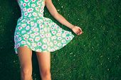 image of lie  - A young woman wearing a flowery dress is lying on the grass in summer - JPG