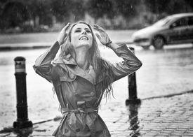 pic of rainy weather  - Beautiful woman wearing a coat posing in the rain - JPG