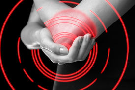 image of elbow  - Unrecognizable woman holds her elbow joint acute pain in the elbow monochrome image pain area of red color - JPG
