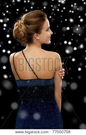 people, holidays and glamour concept - smiling woman in evening dress over black snowy background from back