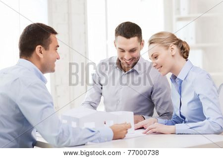 home, design and architecture concept - couple looking at blueprint and model of their new house at office