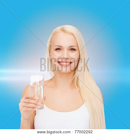 health and beauty concept - young smiling woman with glass of water