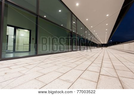 Illuminated Pedestrian Passage Perspective Along Glass Building Facade