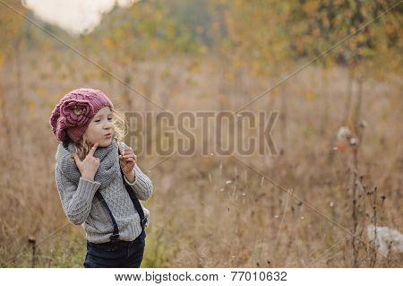 Cute child girl in autumn field with blowball