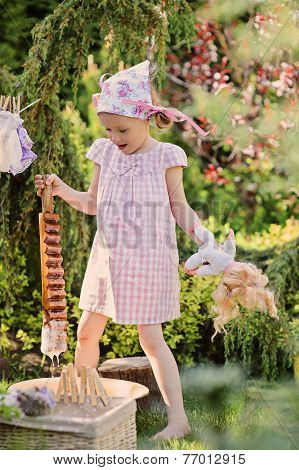 Cute child girl playing toy wash in summer garden