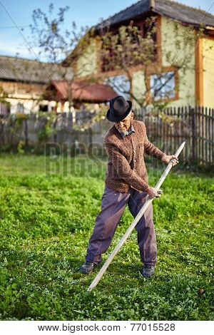 Senior Farmer Mowing The Yard