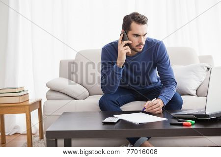 Young man paying his bills with laptop at home in the living room