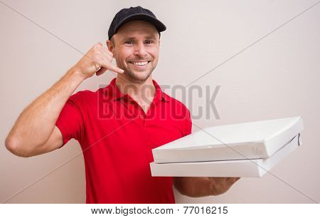 Pizza delivery man making phone call gesture in front of house