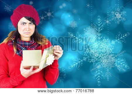 Unhappy brunette opening christmas gift against blue snow flake pattern design