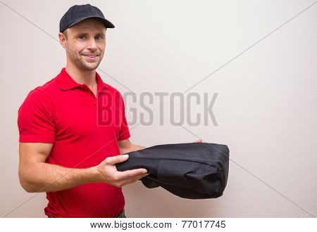 Portrait of delivery man holding pizza in thermal bag