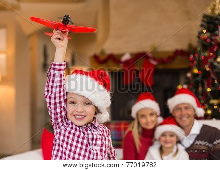 Boy playing with toy airplane in front of his family on couch at home in the living room