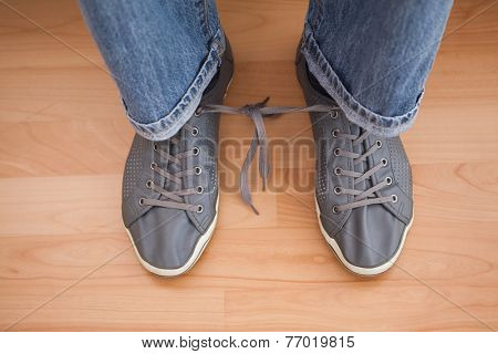 Casual mans shoelaces tied together at home in the living room