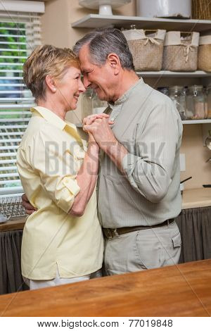 Romantic senior couple dancing together at home in the kitchen