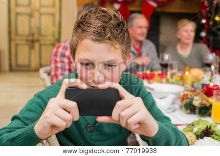 Young boy holding smartphone during christmas dinner at home in the living room