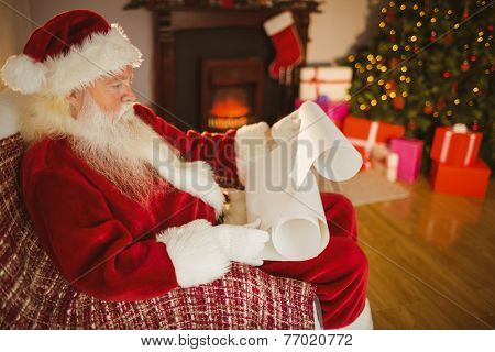 Santa claus reading his list at christmas at home in the living room
