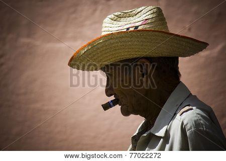 Man Smoking A Cuban Cigar.