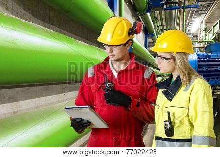 two maintenance engineers going through a checklist during a routine inspection of an industrial installation in a factory