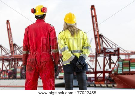 Two dockers looking at an industrial harbor and container terminal, where container ships are being loaded and unloaded