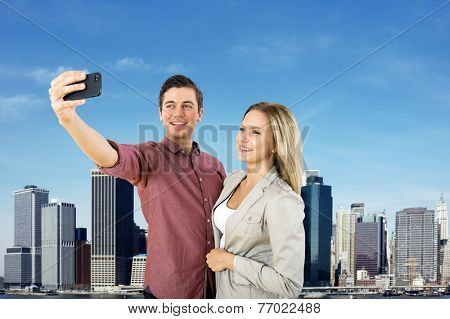 Young urban couple taking a selfie in front of the New York City Skyline