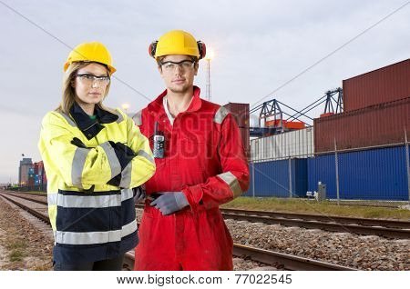 Two rail transport transit guards, posing in front of a container lot along rail tracks