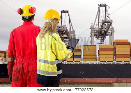 Two dockers with an electronic tablet inspecting a Container ship being unloaded by two large cranes  in the Rotterdam Harbor
