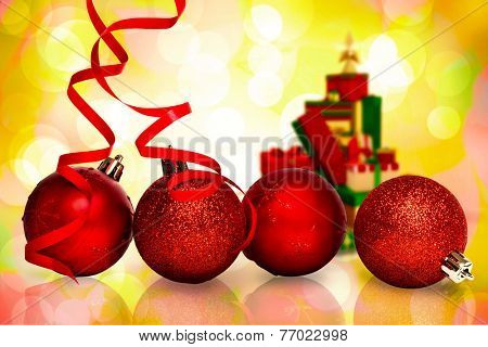 Four red christmas ball decorations against girly pink and yellow pattern